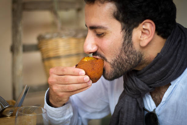 Sicily: Young Man Eating Traditional Arancina (Croquette) stock photo