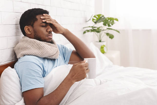 Sick african-american man drinking hot healing tea in bed Feeling bad. Sick african-american man drinking hot healing tea in bed, touching his forehead, empty space male likeness stock pictures, royalty-free photos & images