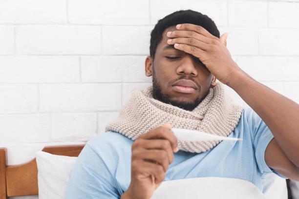 침대에서 체온을 측정 하는 아픈 아프리카계 미국인 남자 - 온도 뉴스 사진 이미지
