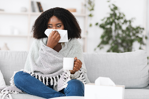 Fever, Cold, Flu Symptoms And Folk Medicine. Sick ill black woman covered in blanket blowing her running nose in a tissue sitting on sofa, drinking hot tea, holding cup, copy space. Taking medication