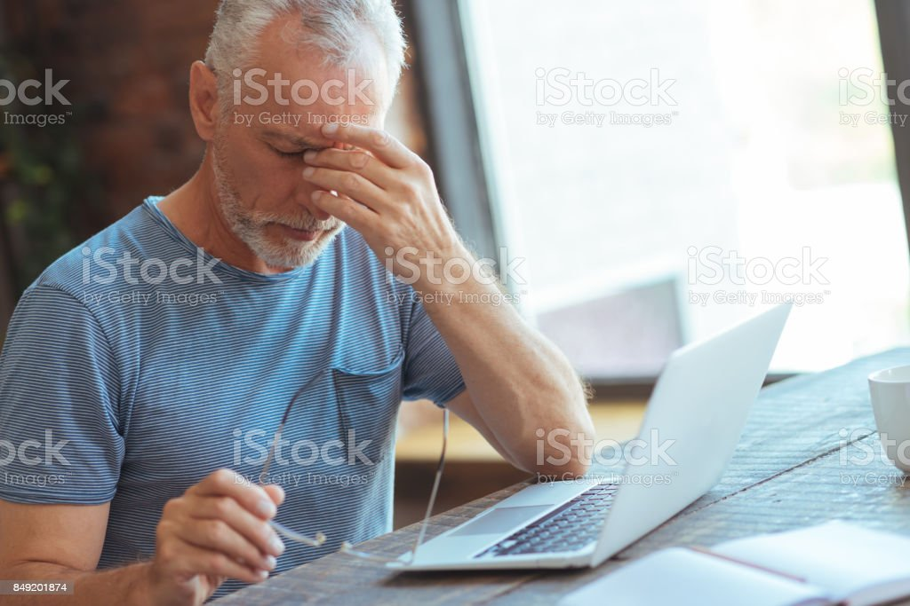 Sick aged man sitting at the table stock photo