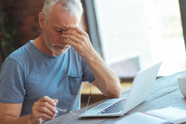 sick aged man sitting at the table - headache stock pictures, royalty-free photos & images