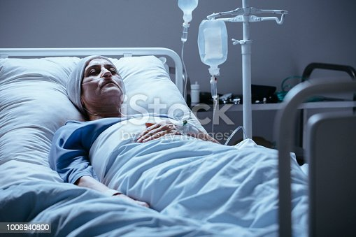 910488902istockphoto Sick and lonely senior woman with leukemia during chemotherapy in the hospital 1006940800