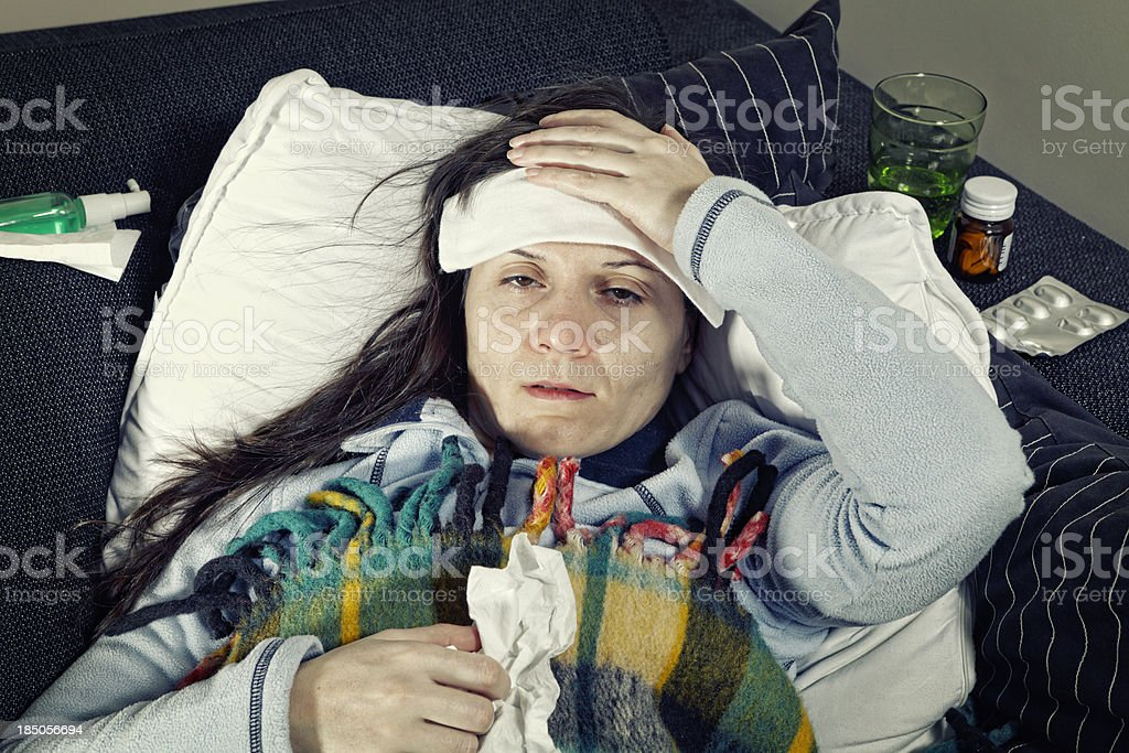 sick and lying on the couch stock photo