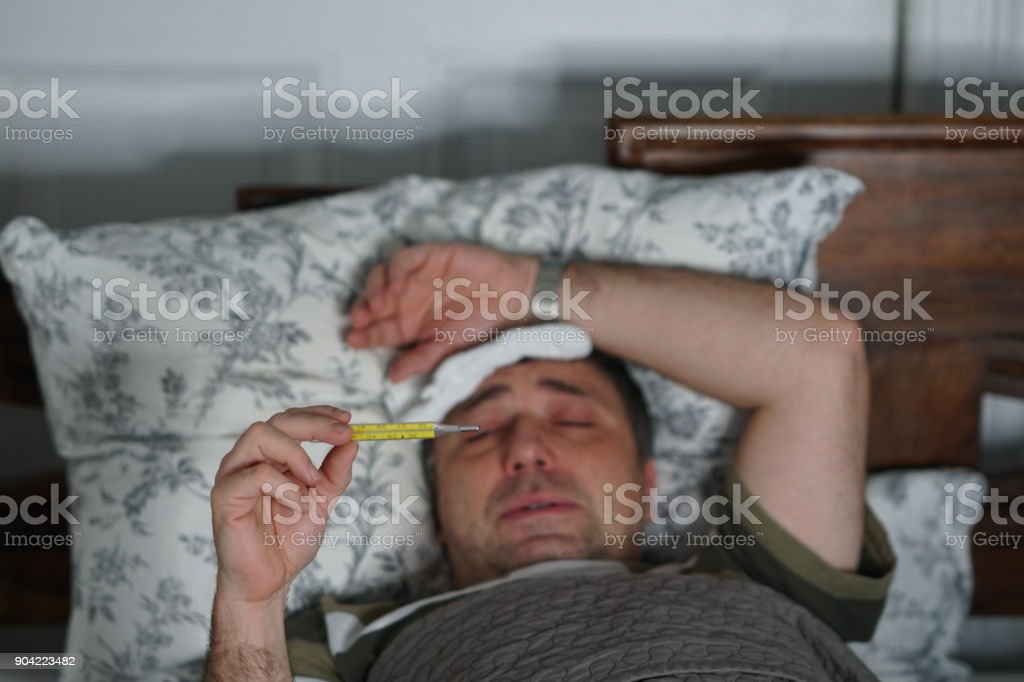 Ziek En Moe Man Liggend In Bed Zijn Temperatuur Controleren