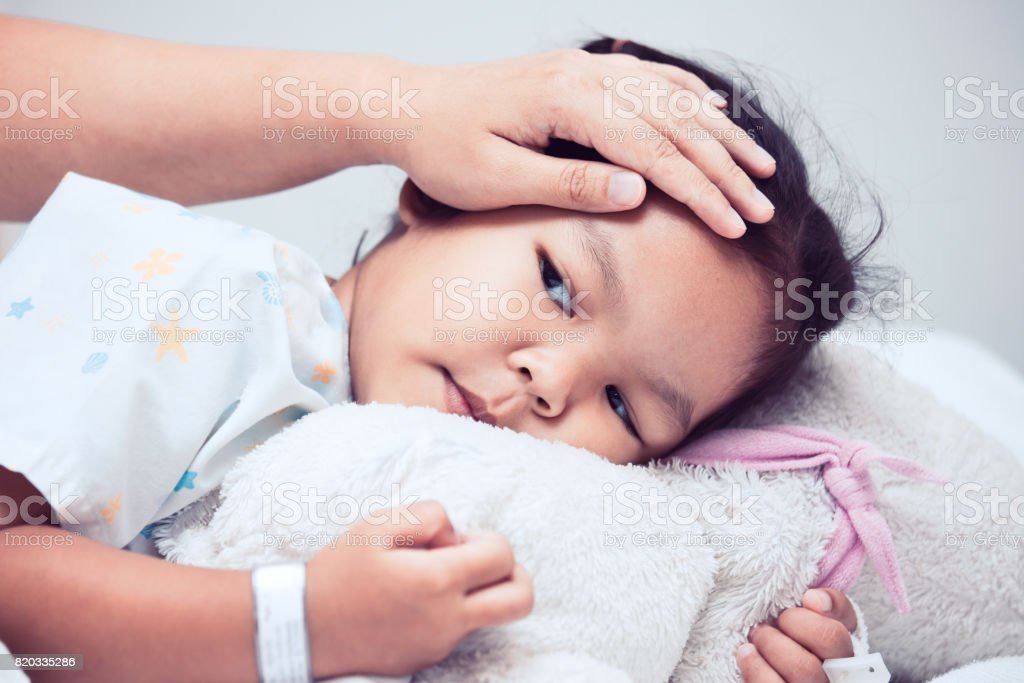 Sick asian child girl is lying in the bed and mother hand touch her forehead with love stock photo