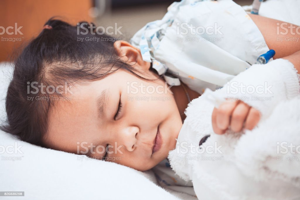 Sick asian child girl is sleeping in the hospital stock photo
