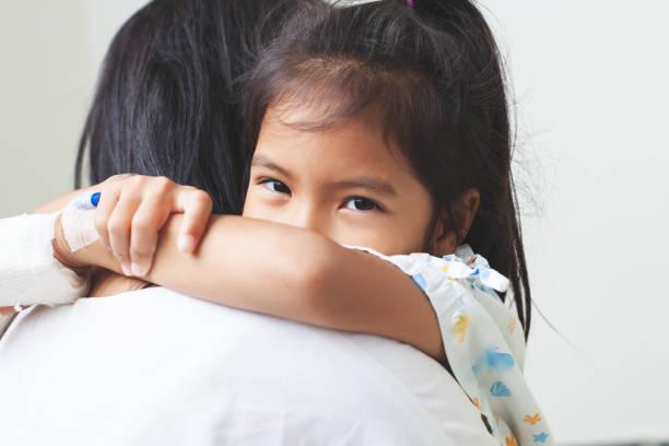 Kranke asiatische Kind Mädchen, die IV Lösung bandagiert umarmt ihre Mutter mit Liebe im Krankenhaus haben – Foto