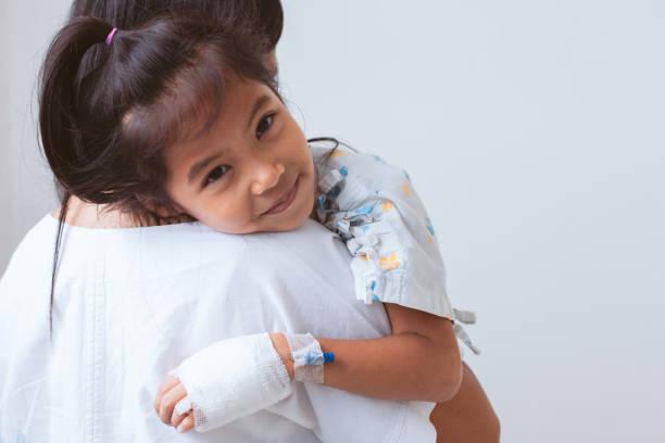 Kranke asiatische Kind Mädchen, die IV Lösung bandagiert lächelnd und umarmt ihre Mutter mit Liebe im Krankenhaus haben – Foto
