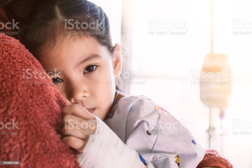 Sick asian little child girl who have IV solution bandaged hugging her mother stock photo