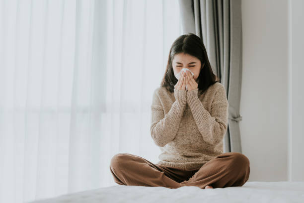 Sick Asian woman using a tissue to sneeze stock photo