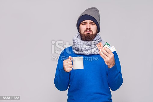 istock Sick bearded man holding cup with tea, many pills. 885311388