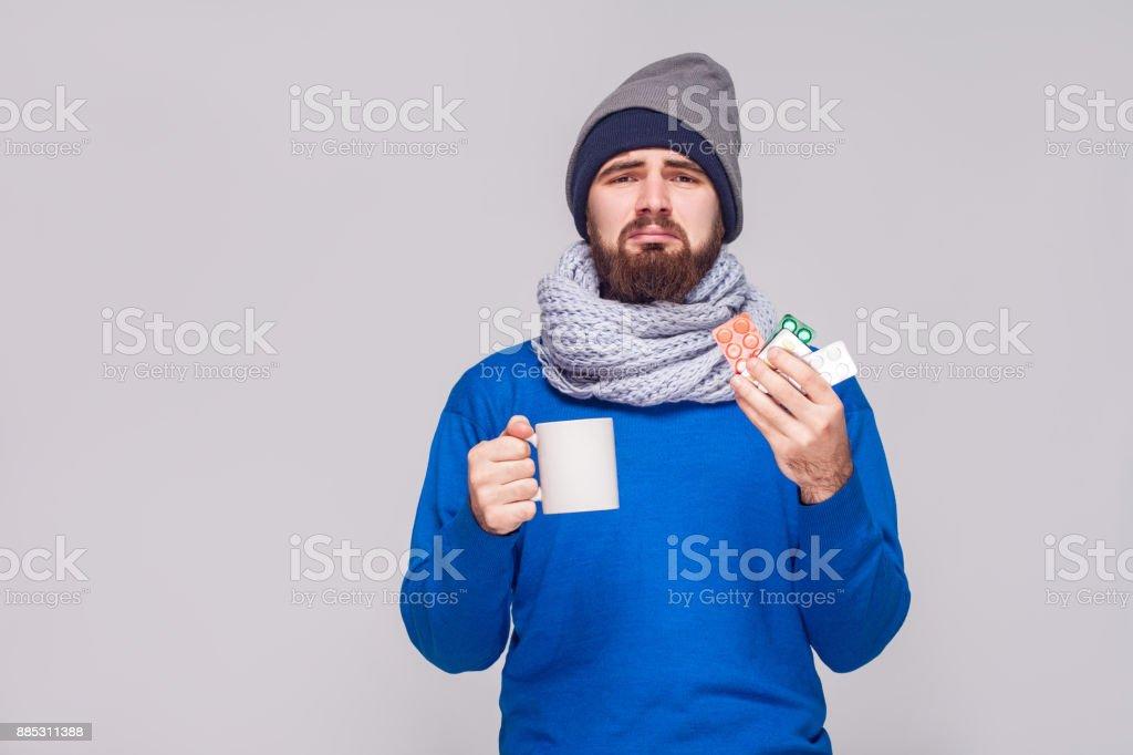 Kranker bärtigen Mann halten Tasse mit Tee, viele Pillen. – Foto