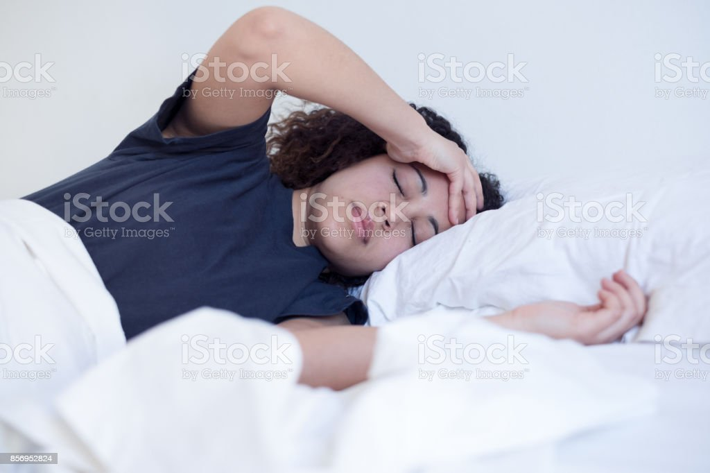 Sick black woman lying in the bed stock photo