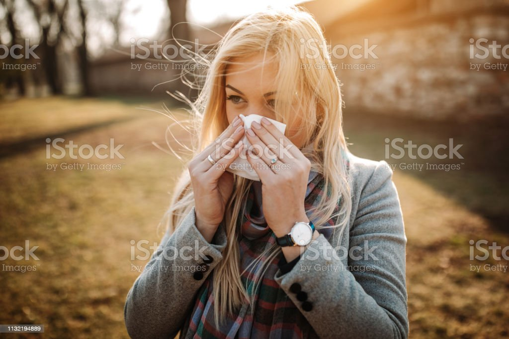 Sick blonde blowing her nose stock photo