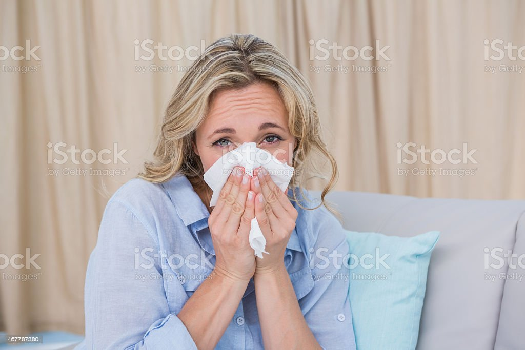Sick blonde on couch sneezing stock photo