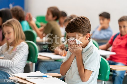 Portrait of a sick boy at the school blowing his nose in class - lifestyle concepts