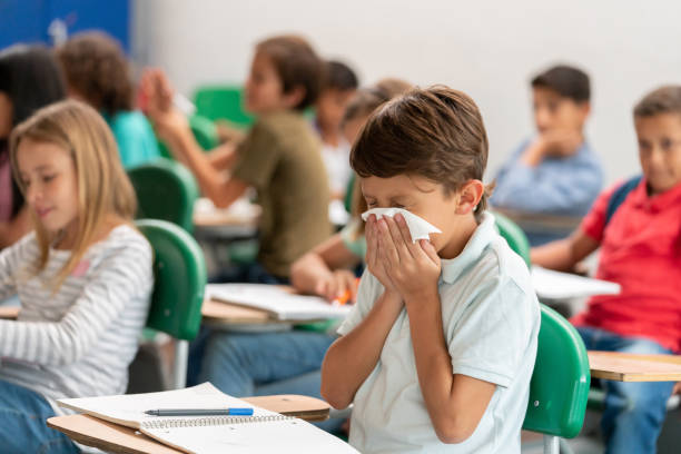 Sick boy at the school blowing his nose in class Portrait of a sick boy at the school blowing his nose in class - lifestyle concepts allergy stock pictures, royalty-free photos & images