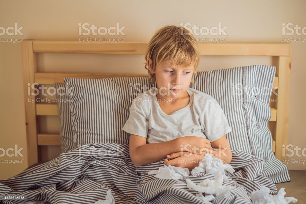 Sick boy coughs and wipes his nose with wipes. Sick child with fever...