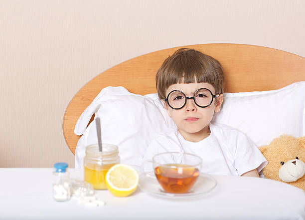 Sick boy in his bed stock photo