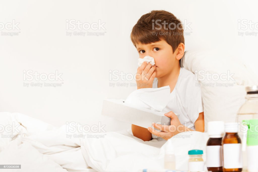 Sick boy sitting in bed and using paper napkins stock photo