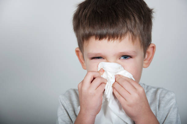 sick child blows his nose in a handkerchief stock photo