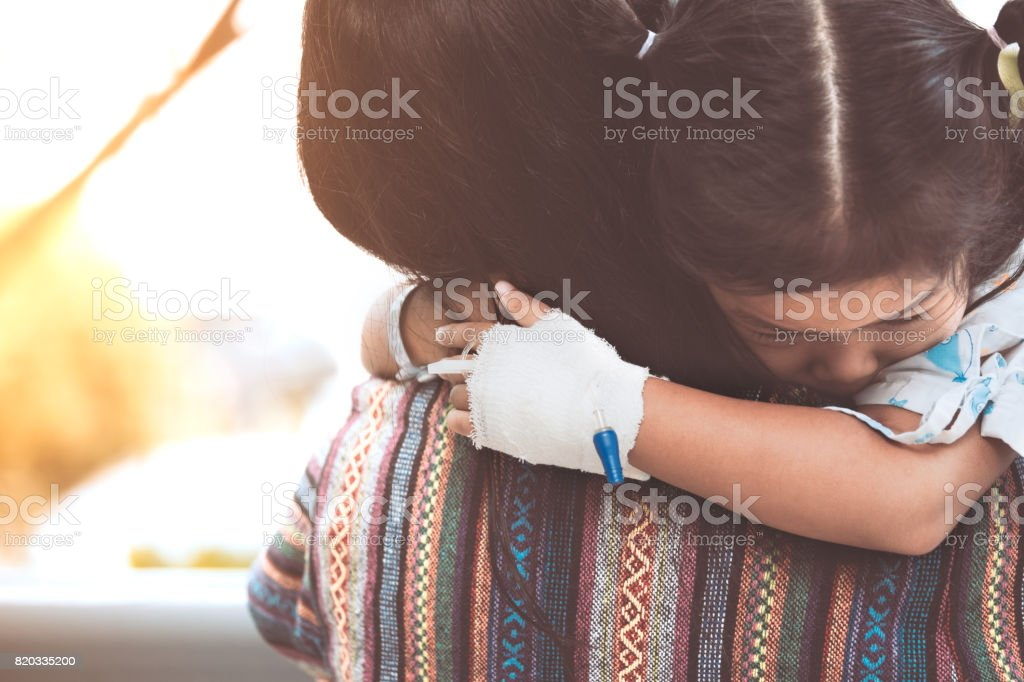 Sick child girl hugging and resting on her mother's shoulder  in the hospital royalty-free stock photo
