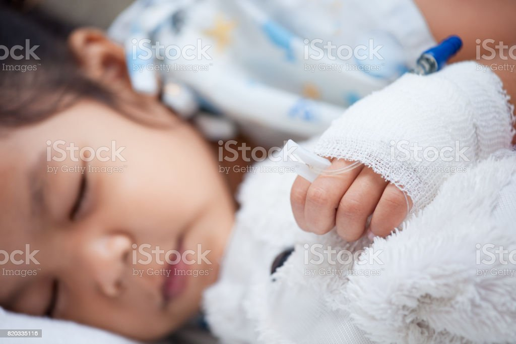 Sick child girl's hand with saline intravenous (iv) drip hugging her doll while sleeping stock photo