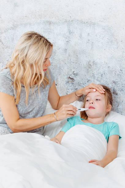 Krankes Kind im Bett - Mutter sorgt sich um ihr Kind – Foto