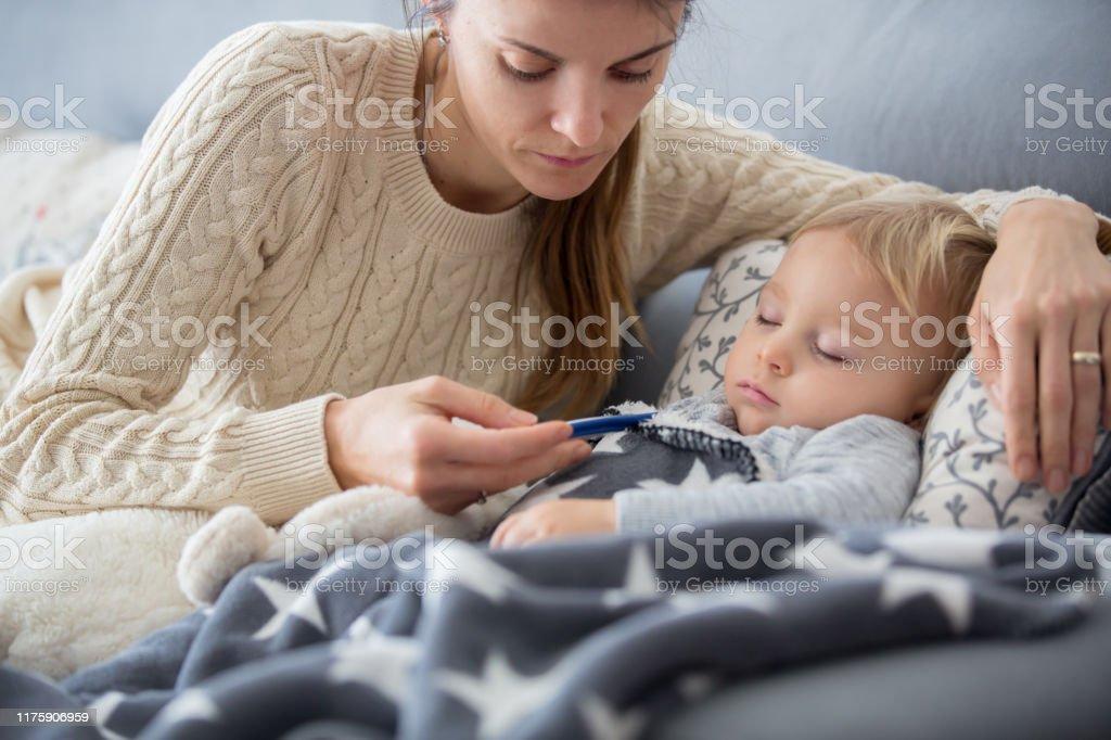 Niño enfermo, niño pequeño acostado en la cama con fiebre, descansando en casa - Foto de stock de Acostado libre de derechos
