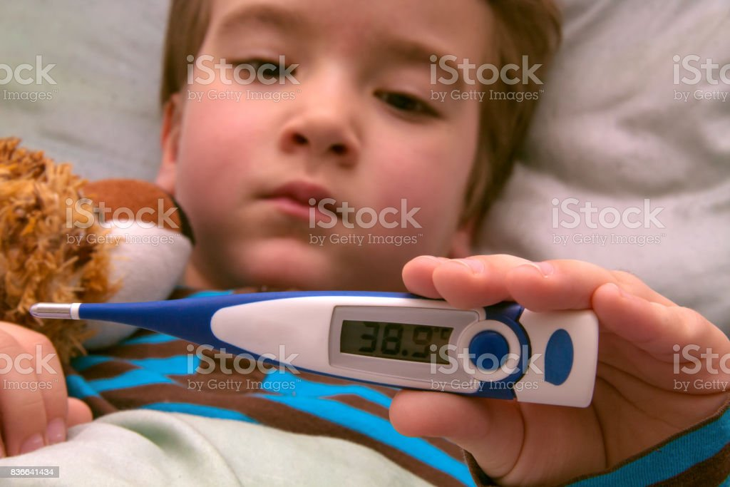 Sick child with high fever resting in bed stock photo