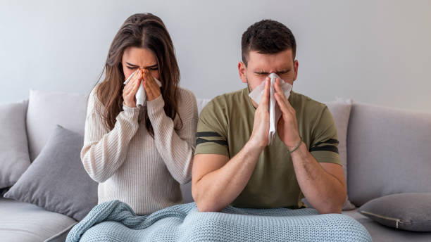 Sick couple are trying to sneeze in the napkin Sick couple are trying to sneeze in the napkin. They caught a cold and now have to take some medicine to get better. Close up. Sick together. Close-up Of Sick Couple Sneezing In Tissue At Home cold virus stock pictures, royalty-free photos & images