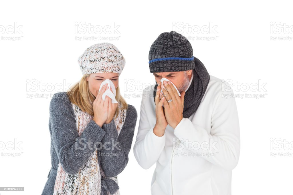 Sick couple in winter fashion sneezing stock photo