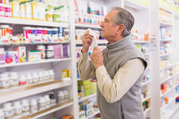 Sick customer holding a tissue Sick customer holding a tissue in the pharmacy human parainfluenza virus stock pictures, royalty-free photos & images