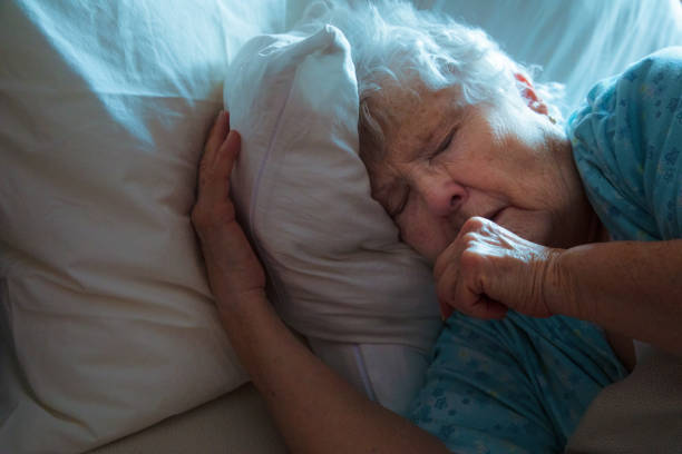 Sick Elderly Woman in bed coughing Sick Elderly Woman in bed coughing, turning away from the light, frowning from discomfort. mucus stock pictures, royalty-free photos & images