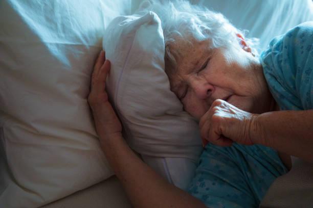 Kranke ältere Frau im Bett Husten – Foto