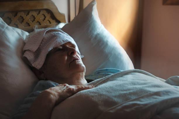 Kranke erschöpfte Seniorin im Bett mit nassem Waschlappen auf der Stirn – Foto