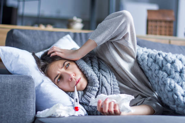 Sick female with cold and flu. Health care concept Sick exhausted girl in scarf is lying in bed wrapped in blanket. Young woman with fever and headache is measuring temperature with thermometer, treated at home. Winter cold and flu concept. flu stock pictures, royalty-free photos & images