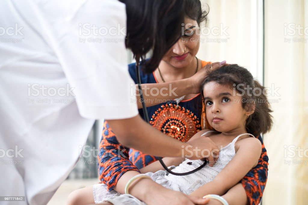 Sick girl at a check up with her mother stock photo