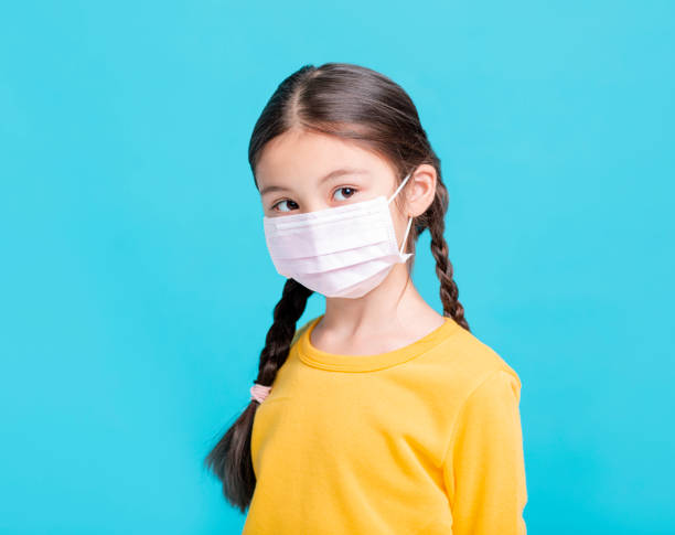 enfant malade de fille dans le masque médical d'isolement sur le fond bleu - masque enfant photos et images de collection