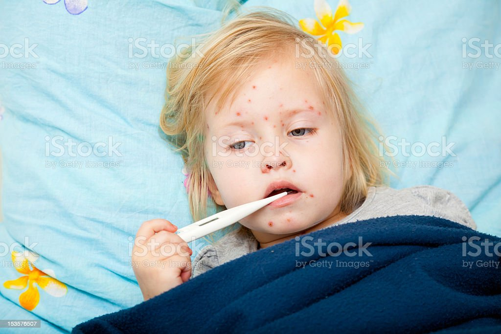 Sick girl is measuring the temperature a sick cute girl is measuring the temperature Adversity Stock Photo