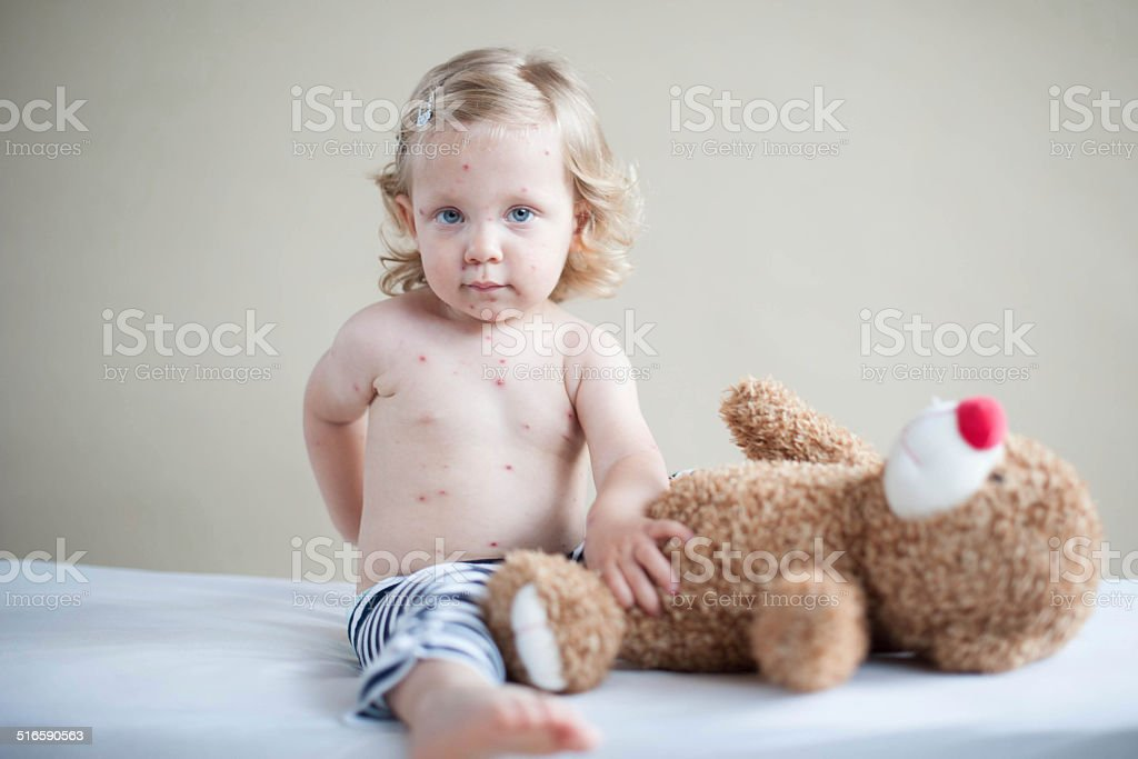 Sick girl is sitting on the bed with teddy-bear stock photo