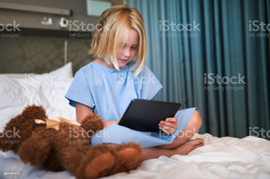 Sick girl using digital tablet while sitting on hospital bed. Little...