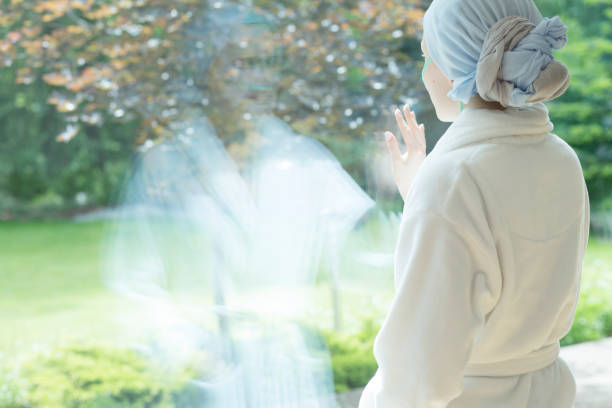 Sick girl with cancer touching window in the hospice during treatment Sick girl with cancer touching window in the hospice during treatment chemotherapy cancer stock pictures, royalty-free photos & images