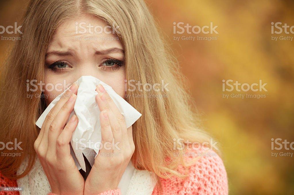 Sick ill woman in autumn park sneezing in tissue. stock photo