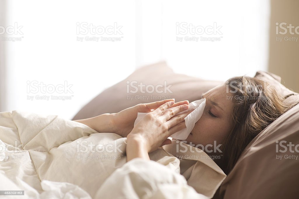 Sick in Bed Young sick woman blowing her nose while in bed Adult Stock Photo