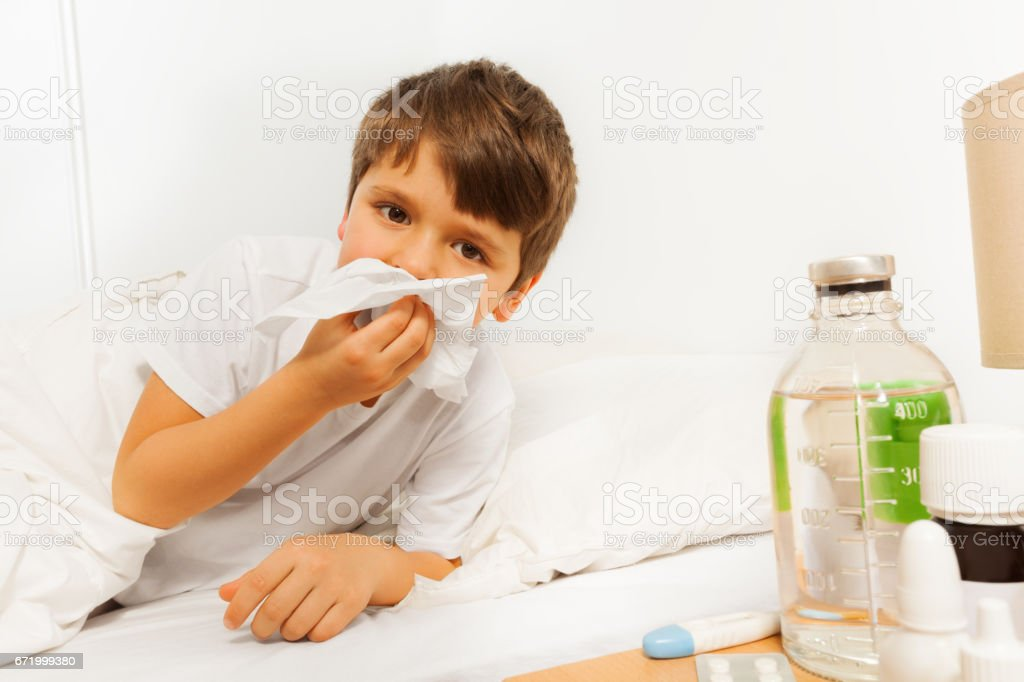 Sick kid boy blowing his nose with a napkin stock photo