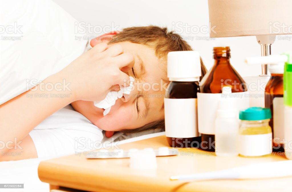 Sick kid boy with bad cold using paper napkins stock photo