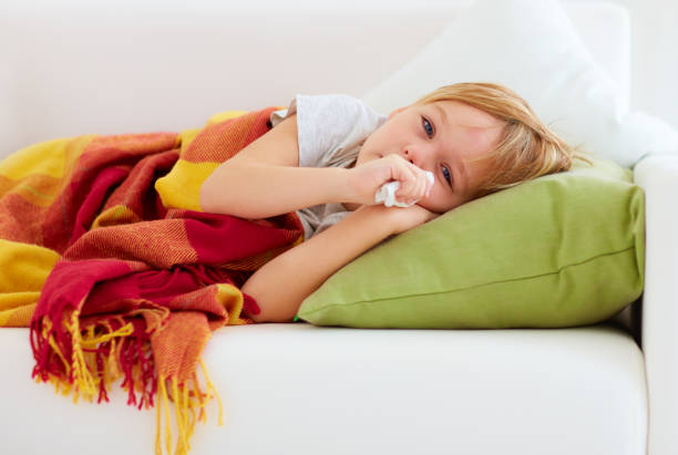 sick kid with runny nose and fever heat lying on couch at home - infezione respiratoria foto e immagini stock