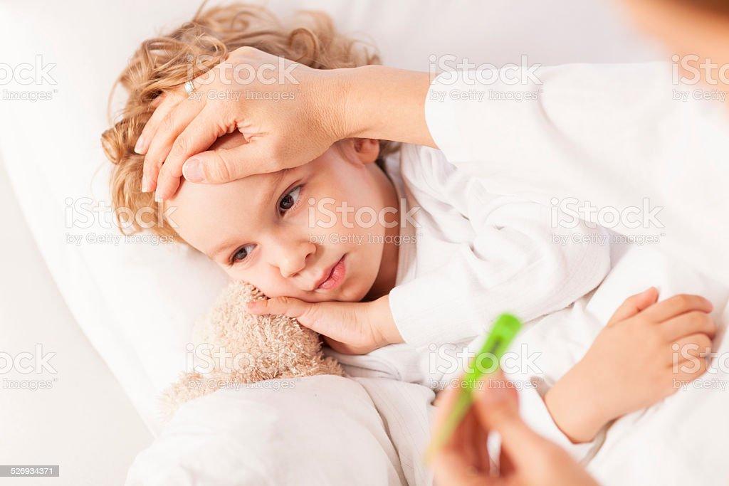 Sick little boy having his body temperature measured stock photo